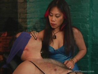 Aged Asian Dominatrix Sits Submissive Male on the Bondage Chair