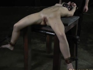 Disobedient girl is lying on the table chained with gag in her mouth