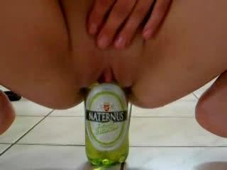 Amateur fucks a beer bottle in kitchen
