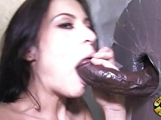 Tattooed black haired pornstar sucks black glory hole cock