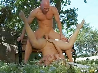 Muscled bald stud drilling breasty blonde on bench in park