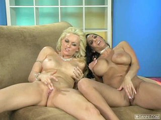 Busty cock tease Monica Mayhem plays with a girlfriend on the couch